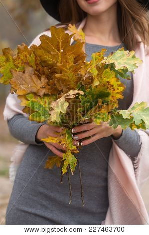 Woman With A Bouquet Of Oak Branches In Autumn