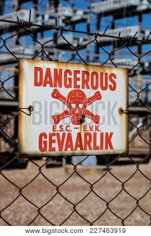 Danger Sign On A Fence Outside An Electrical Facility For Energy Transmutation