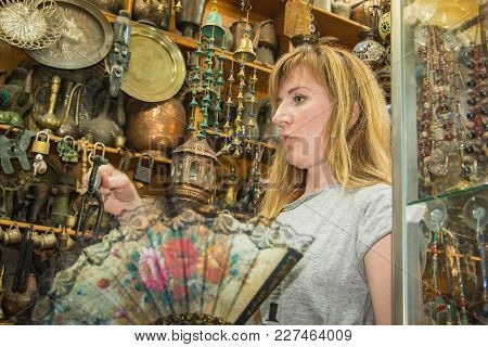 Akaba, Jordan -december 23, 2017: Female Tourist Is Buying A Souvenirs In An Antique Shop
