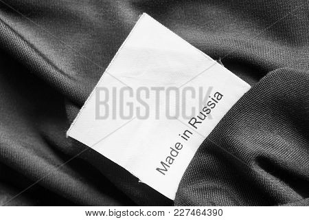 Clothes Label Lettered Made In Russia On Black Sain Background Closeup