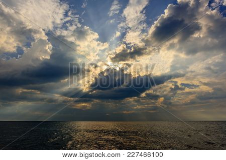The Rays Of The Sun, Breaking Through Thunderclouds In The Blue Sky Over The Ocean With The Yellow R