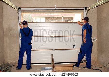 Kyiv, Ukraine - February, 20, 2018: Contractors Installing, Repair, Insulating Garage Door. Garage D