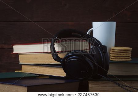 White Cup With Hot Coffee, Cookies And Headphones On Deployed Books On A Dark Wooden Background