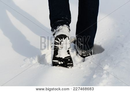 Male Legs In Winter Shoes Walking On Snow Covered Path . Close -up .