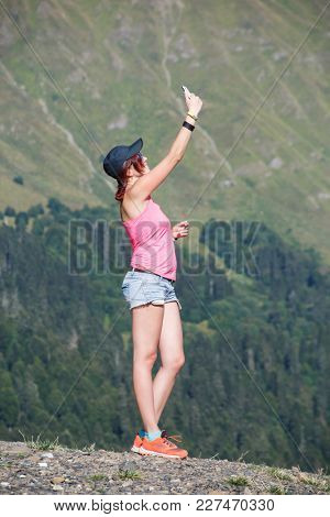 Photo of girl taking pictures of herself againstof mountains