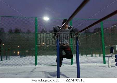 Image of athlete in black hat pulling up on bar in evening