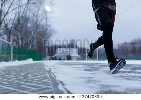 Picture of athlete running in sneakers at stadium in winter