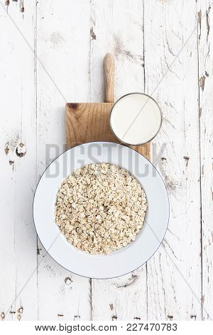 Oatmeal, rolled oats on white wooden background wilt glass of milk. Porridge oats, used in granola or muesli. Breakfast concept poster
