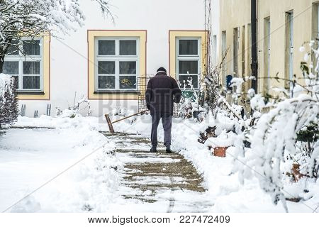Man Sweeping Snow From The Pavement After The Storm