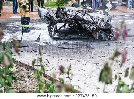 Burned Car After An Accident On The Road. Firefighters Standing Nearby. Reportage Picture Crowd In B