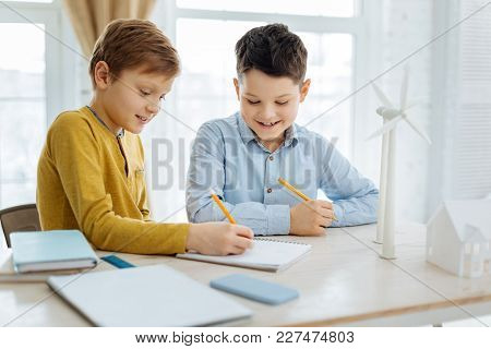 Gaining Knowledge. Upbeat Pre-teen Boys Sitting At The Table And Sketching Wind Turbines In Their No