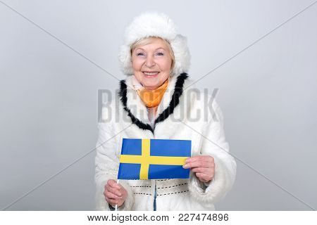 Senior Woman Holding A Flag Of Sweden. Adult Woman Is 70 Years Of Age. Pensioner. Old Female Is Dres