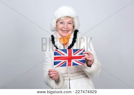 Senior Woman Holding A Flag Of The Great Britain. Adult Woman Is 70 Years Of Age. Old Female Is Dres