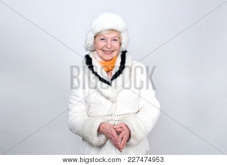 Adult Woman Is 70 Years Of Age. Pensioner. Old Female Is Dressed In Warm Winter Clothes Standing On