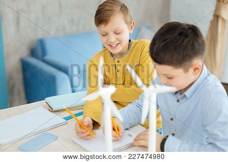 Future Of Engineering. Upbeat Pre-teen Boys Sitting At The Table Together And Drawing The Sketches O
