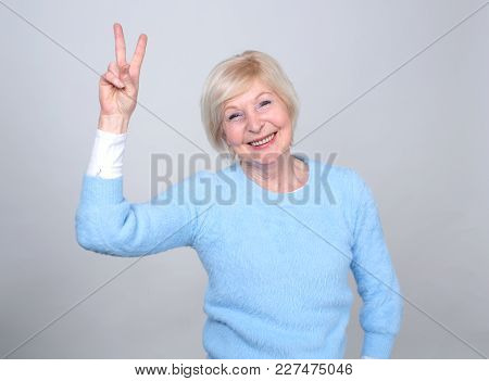 Senior Woman 70 Years Of Age. Adult Woman Shows A Gesture With Two Fingers Of A Symbol Of Luck And V
