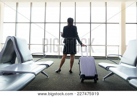 Image Of Businesswoman At Airport Looking At Airplane Taking Off, Business