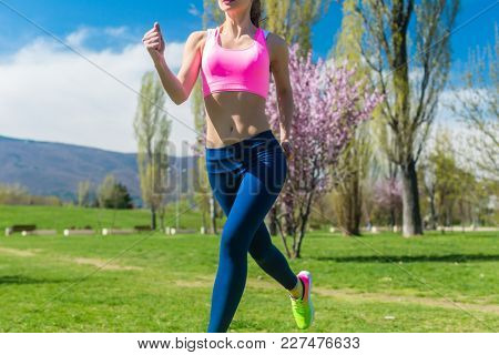 Torso of fit woman running or jogging on spring day