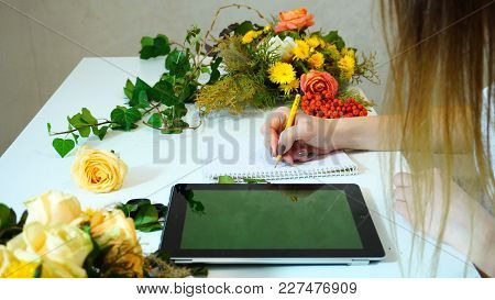 Girl Florist Sketches In Notebook With Pencil Idea Of Bouquets And On Tablet Compiles List Of Plants