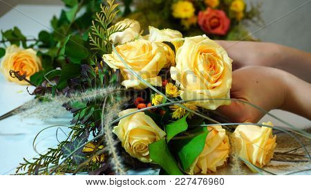 Hands Of Young Woman Designer Flower Arrangements That Inserts Branches Of Bright Orange Mountain As
