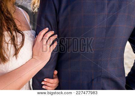 Golden Wedding Ring In Hand Of Woman. Bride Hugging The Groom In Suit