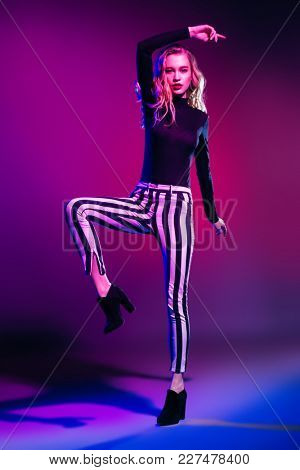 Attractive fashionable young woman wearing in hat, striped trousers and boots. Youth style. Studio shot.