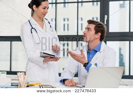 Young female physician using a tablet PC while asking for advice from her experienced male colleague in the office a modern hospital