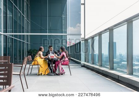 Three Indian business people with worried facial expression talking during break at work