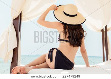 Woman in swimwear lounging on beach in her vacation relaxing