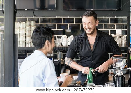 Cheerful bartender cleaning the portafilter of an espresso machine while talking with a young customer in the coffee shop