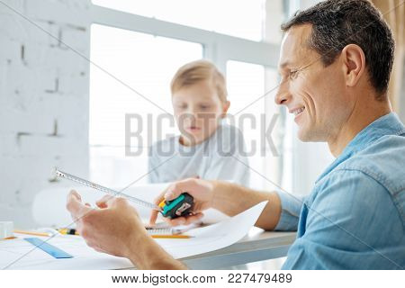 Useful Tool. Handsome Young Engineer Sketching A Blueprint And Using The Tape Measure, Checking The