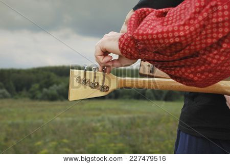 Setting Up The Balalaika With Your Hands. Street Public Concert Of Folk Music.