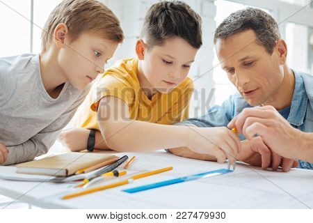 Explaining Clearly. Caring Young Father Holding A Compass And Showing His Sons How To Use It Correct
