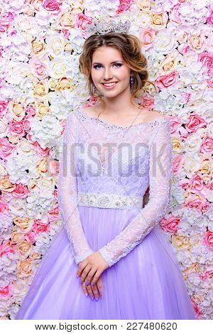 Charming bride in a beautiful dress and a crown posing by a background of roses. Wedding fashion.