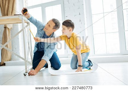 Best Team. Cheerful Charming Young Father Working On A Table Construction Together While The Man Mea