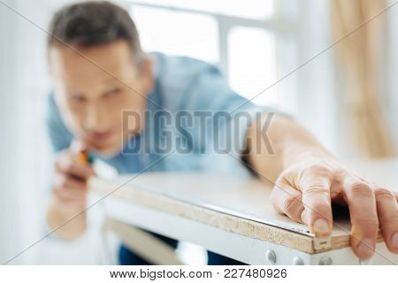 Thorough Carpenter. The Focus Being On The Hand Of A Young Man Using A Tape Measure And Fixing It On