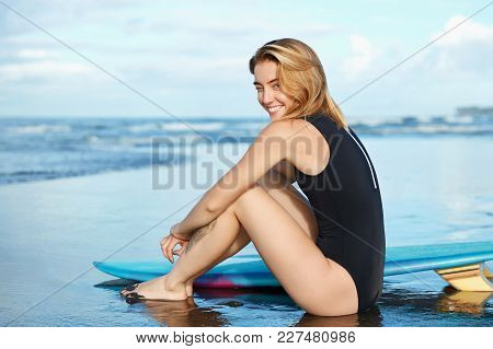 Professional Female Athlete Surfer Sits At Coastline With Surfboard, Waits Waves On Ocean Beach, Has
