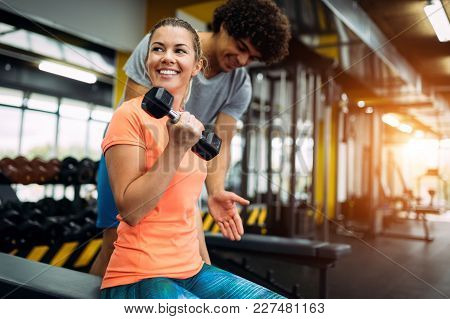 Young Beautiful Woman Doing Exercises With Personal Trainer In Gym