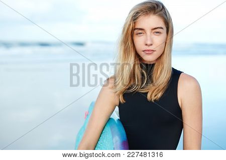 Serious Blonde Female Model In Black Swimsuit Poses With Surf Board Against Blue Ocean View, Being S
