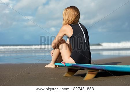 Image Of Unrecognizable Female In Black Swimsuit, Sits Back On Sand, Looks Attentively At Calm Ocean