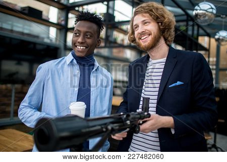 Two happy modern businessman with telescope looking straight and smiling