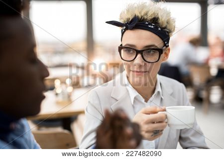 Serious woman in eyeglasses and headband having tea or coffee and listening to her colleague during conversation