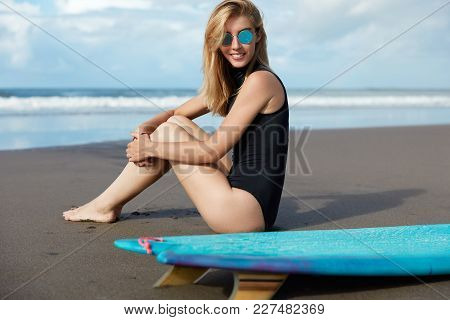 Rear View Of Pleasant Looking Skilled Female Surfer In Swimsuit, Sits On Coastline, Wears Trendy Sun