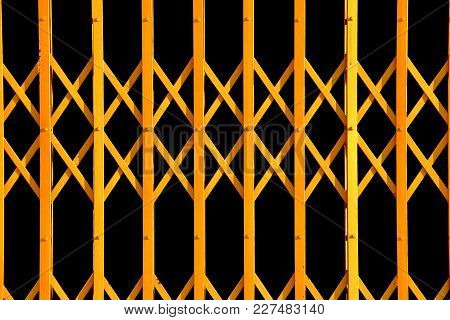 Yellow Geometric Pattern From Folding Gate, Ancient Yellow Expanded Metal Door On Black Background