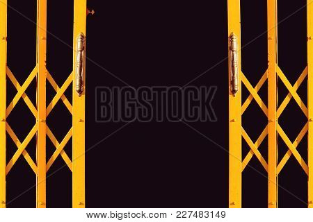 Yellow Folding Gate, Ancient Yellow Expanded Metal Door On Black Background