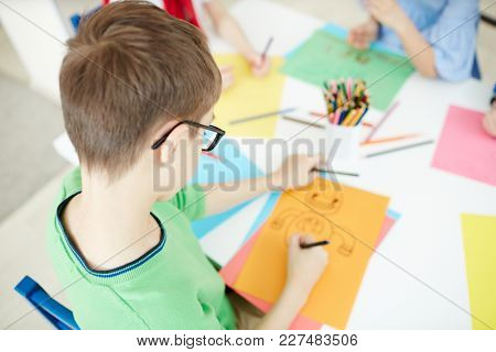 Overview of diligent schoolboy drawing with crayons on yellow paper at lesson
