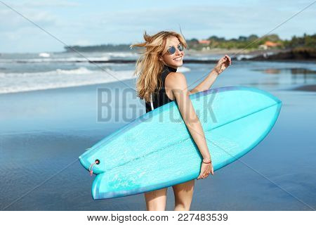 Happy Female Dressed In Black Swimsuit, Wears Trendy Sunglasses, Being In Good Mood As Going To Surf