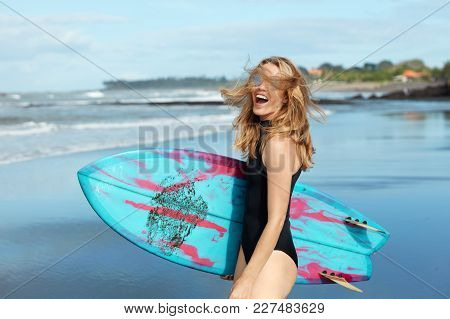 Pretty Blonde Young Woman Laughs Happily Outdoor, Dressed In Black Swimsuit, Holds Surf Board Agains