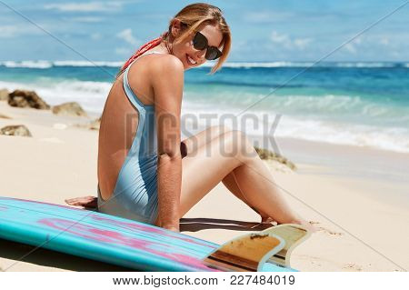 Adorable Beautiful Young Female Model Wears Sunglasses And Bathing Suit, Sits On Hot Sandy Beach Aga