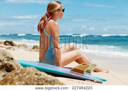 Dreamy Blonde Woman In Blue Bathing Suit And Sunglasses, Sits On Hot Sandy Beach, Looks Into Distanc